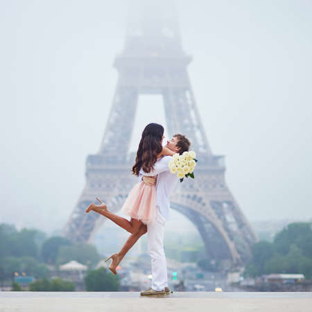 Photo for Happy couple with white roses near the Eiffel tower in Paris. Tourists enjoying their vacation in France. Romantic date or traveling couple concept - Royalty Free Image