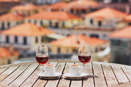Photo pour Two glasses of Madeira wine and two cups of fresh espresso coffee in street cafe with view to Funchal town, Madeira, Portugal - image libre de droit