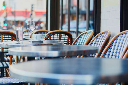 Photo pour Empty coffee cup and glass of water in an outdoor cafe in Paris, France - image libre de droit