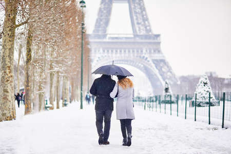 Foto de Couple of tourists walking in Paris under umbrella on a day with heavy snow. Unusual weather conditions in Paris - Imagen libre de derechos