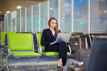 Photo pour Young woman in international airport working on laptop while waiting for her flight - image libre de droit