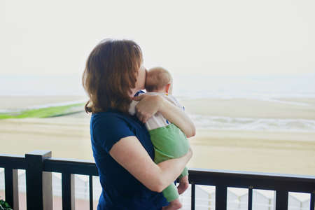Photo pour Mother and child on balcony of their home or hotel room. Woman holding baby girl in her arms and looking at the sea - image libre de droit