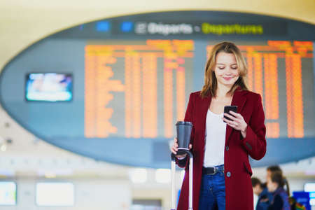 Photo pour Young woman in international airport with luggage and coffee to go waiting for her flight - image libre de droit