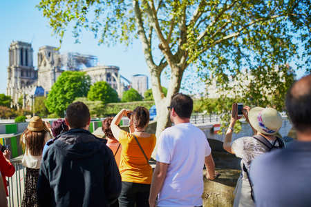Photo pour People taking photos of Notre Dame cathedral without roof and spire destroyed by fire in Paris, France - image libre de droit