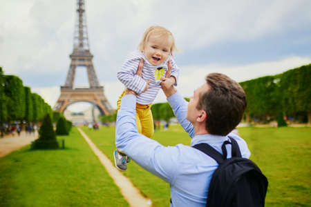 Photo pour Father holding his adorable daughter in Paris near the Eiffel tower. Family on vacation in France. Travelling with kids - image libre de droit
