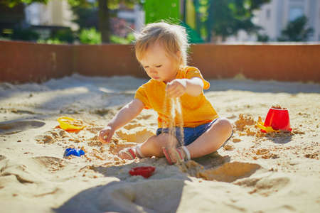 Foto de Adorable little girl on playground in sandpit. Toddler playing with sand molds and making mudpies. Outdoor creative activities for kids - Imagen libre de derechos