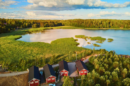 Photo pour Scenic aerial view of colorful boats near wooden berth and buildings in the countryside of Finland at sunset - image libre de droit