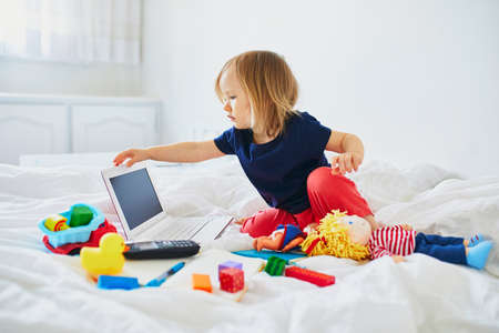 Foto de Toddler girl with laptop, notebook, phone and different toys in bed on clean white linens. Freelance, distance learning or work from home with kids concept - Imagen libre de derechos