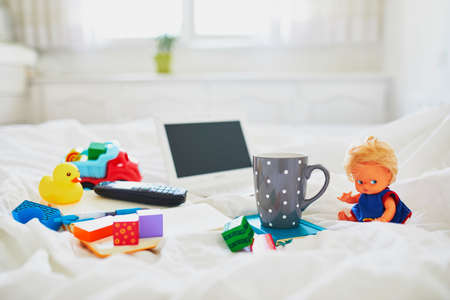Foto de Laptop, cup of coffee, notebook, phone and different toys in bed on clean white linens. Freelance, distance learning or work from home with kids concept - Imagen libre de derechos