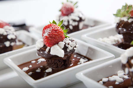 chocolate mudcakes with strawberry on white plates