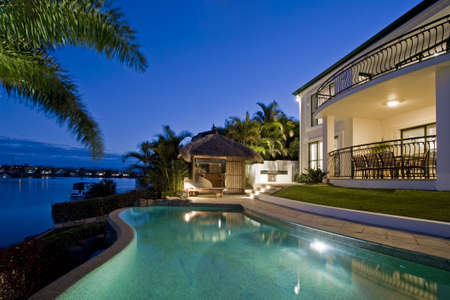 Photo pour Luxurious mansion exterior at dusk overlooking pool, canal and Bali hut - image libre de droit