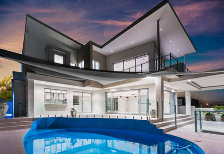 Foto de Modern new luxurious mansion exterior with swimming pool and reflections at dusk with pink and blue sky on the Gold Coast, Queensland, Australia - Imagen libre de derechos