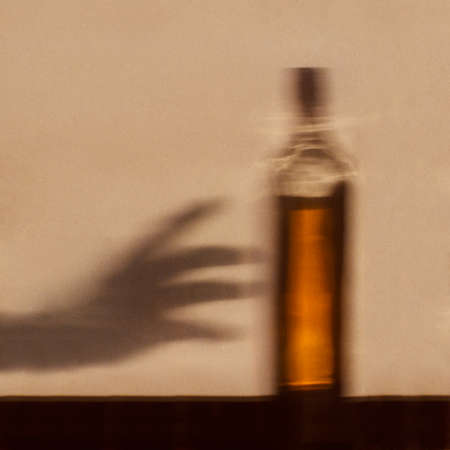 Foto de Alcohol addiction concept - shadow of hand reaching for bottle of alcohol - Imagen libre de derechos