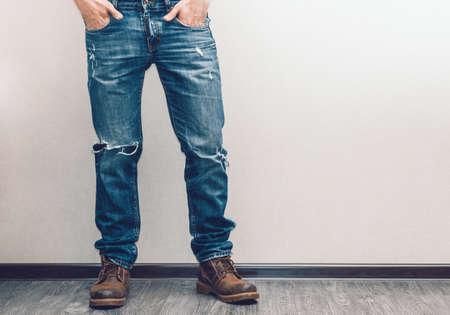 Foto de Young fashion man's legs in jeans and boots on wooden floor - Imagen libre de derechos