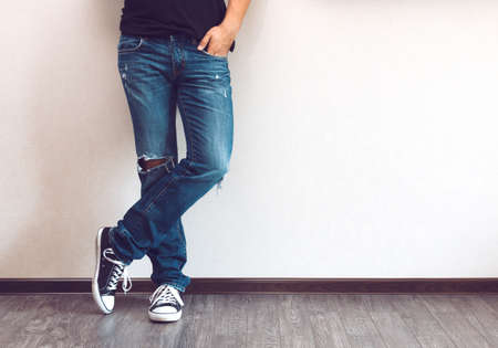 Photo pour Young fashion man's legs in jeans and sneakers on wooden floor - image libre de droit