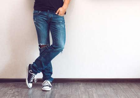 Foto de Young fashion man's legs in jeans and sneakers on wooden floor - Imagen libre de derechos