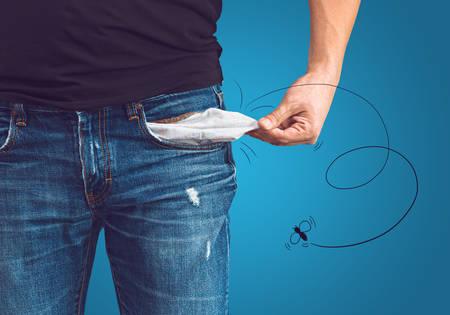 Foto de Poor man in jeans with empty pocket and drawn fly concept - Imagen libre de derechos
