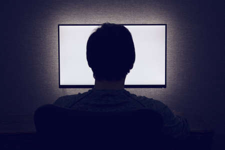 Foto de Man sits in front of a blank monitor in dark room - Imagen libre de derechos
