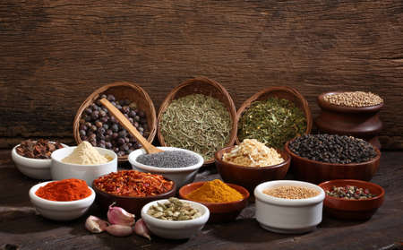 Various bowls of spices over wooden background  Colours and textures