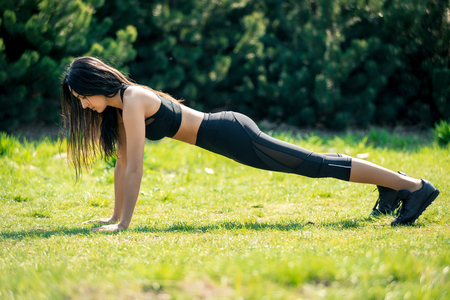 Photo pour Slender beautiful girl with dark hair in a sports form is pressed out on nature, a symbol of a healthy lifestyle, a strong personality and a desire for success and a sports body. Horizontal frame - image libre de droit