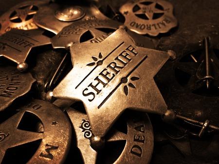 Foto de Sheriff's tin badge in pile of star law enforcement badges - Imagen libre de derechos