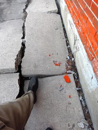Foto de Man walking on broken dangerous cracked sidewalk and brick wall - Imagen libre de derechos