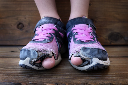 Photo pour Detailed photo of shoes with holes in them and toes sticking out child kid young - image libre de droit