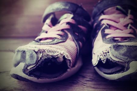 Foto de Old tennis or athletic running shoes with holes in them - Imagen libre de derechos