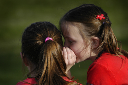 Photo pour Sisters telling secrets friends by whispering in ears to each other - image libre de droit