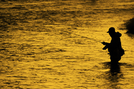 Foto de Silhouette of Fishing Flyfishing rod reel in river with golden sunlight - Imagen libre de derechos