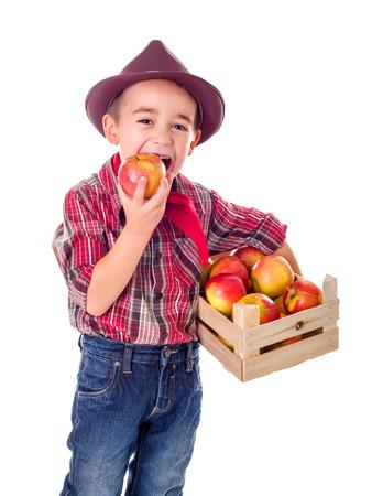 Little casual farmer boy tasting fresh harvested apple