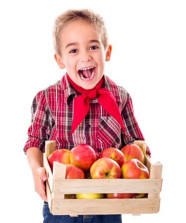 Happy farmer boy holding big crate full of ripe apples