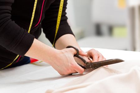 Photo pour Dressmaker cutting fabric with big old steel scissors - image libre de droit