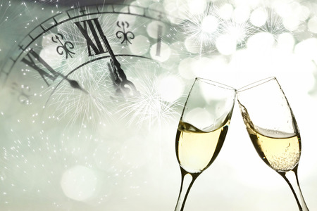 Photo for Glasses with champagne against fireworks and clock close to midnight  - Royalty Free Image