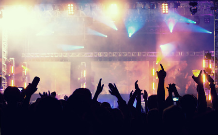 Photo for Cheering crowd in front of bright colorful stage lights - retro styled photo - Royalty Free Image