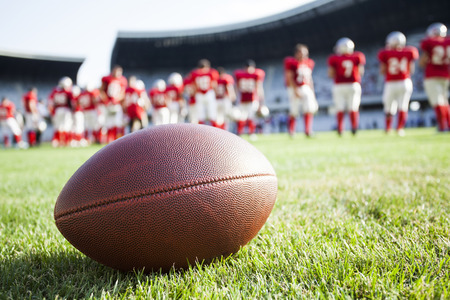 Foto de Close up of an american football on the field, players in the background - Imagen libre de derechos