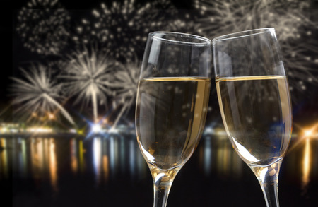 Photo pour Glasses with champagne against fireworks and city lights - image libre de droit