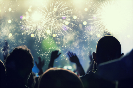 Foto de Cheering crowd and fireworks at New Year's Eve - people celbrating on open air - Imagen libre de derechos