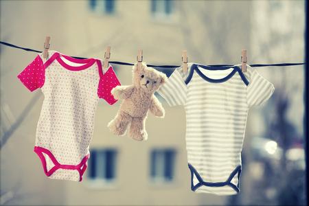 Foto de Baby clothes and a teddy bear hanging on the clothesline - Imagen libre de derechos