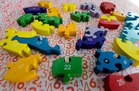 Foto de puzzles and colored figures with numbers and letters used in occupational therapy, for rehabilitation or learning - Imagen libre de derechos