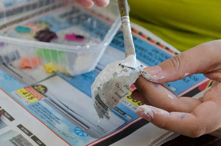 Photo pour A girl painting with acrylic paint a paper mask - image libre de droit