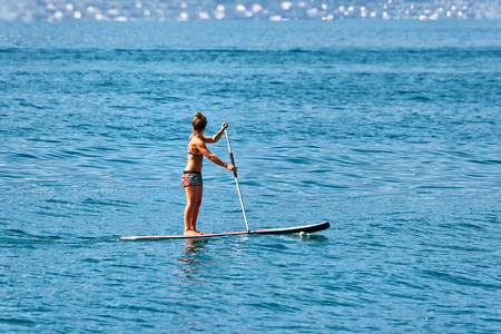 Photo for Girl standing on standup paddle surfing in Geneva Lake in Montreux, Switzerland - Royalty Free Image