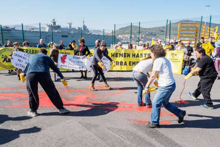 Foto de BILBAO, SPAIN - MARCH / 23/2019. People protesting the arrival of the aircraft carrier of the Spanish Navy Juan Carlos I in the port of Bilbao during open day to visit the ship. - Imagen libre de derechos