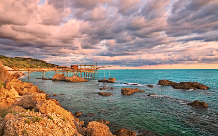 Foto de Rocca San Giovanni, Chieti, Abruzzo, Italy: landscape of the Adriatic sea coast at dawn with a typical Mediterranean fishing hut trabocco, under a dramatic cloudy sky - Imagen libre de derechos