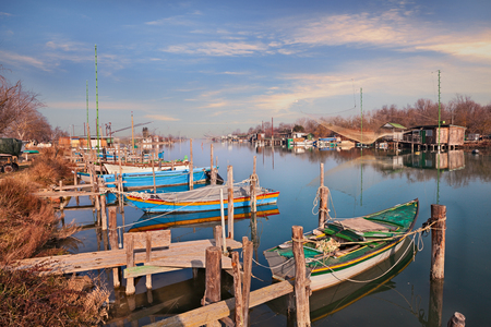Photo pour Ravenna, Emilia Romagna, Italy: landscape of the wetland in the nature reserve Po Delta Park with small boats and fishing huts in the river - image libre de droit