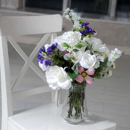 Photo pour Bouquet of artificial roses, phlox and bells on a table in a vase, as an interior decoration - image libre de droit