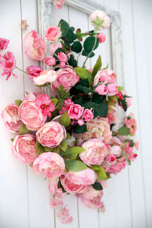 Photo pour A bouquet of pink orchids, roses and peons in a large frame hanging on the wall. - image libre de droit