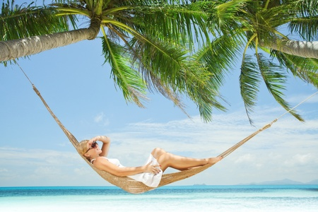 Photo for view of nice young lady swinging  in hummock on tropical beach - Royalty Free Image