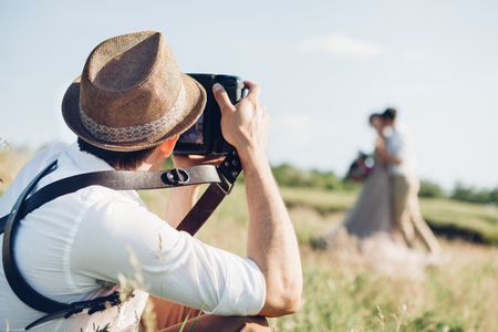 Foto de wedding photographer takes pictures of bride and groom in nature, fine art photo - Imagen libre de derechos