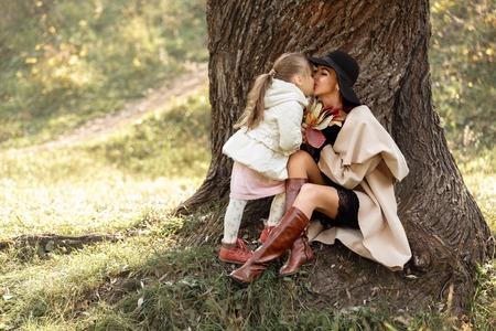Photo pour mother kissing her little daughter girl near the tree - image libre de droit